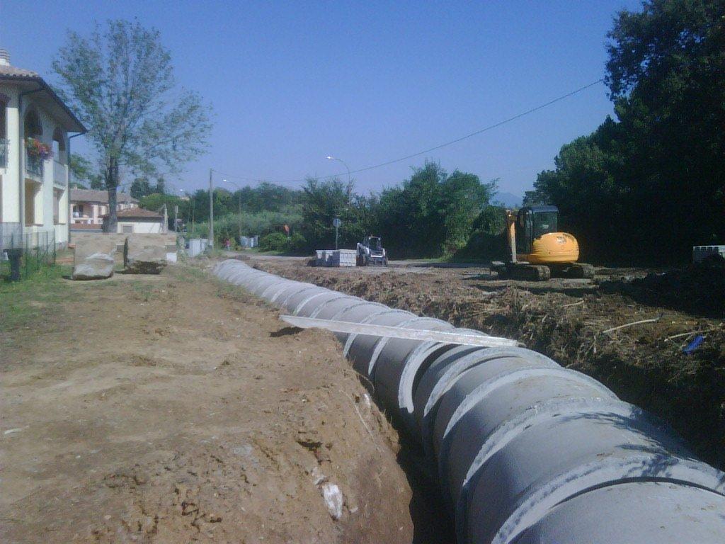 un grosso condotto grigio in un terreno scavato, sulla sinistra delle case e sulla destra dei mezzi da lavoro