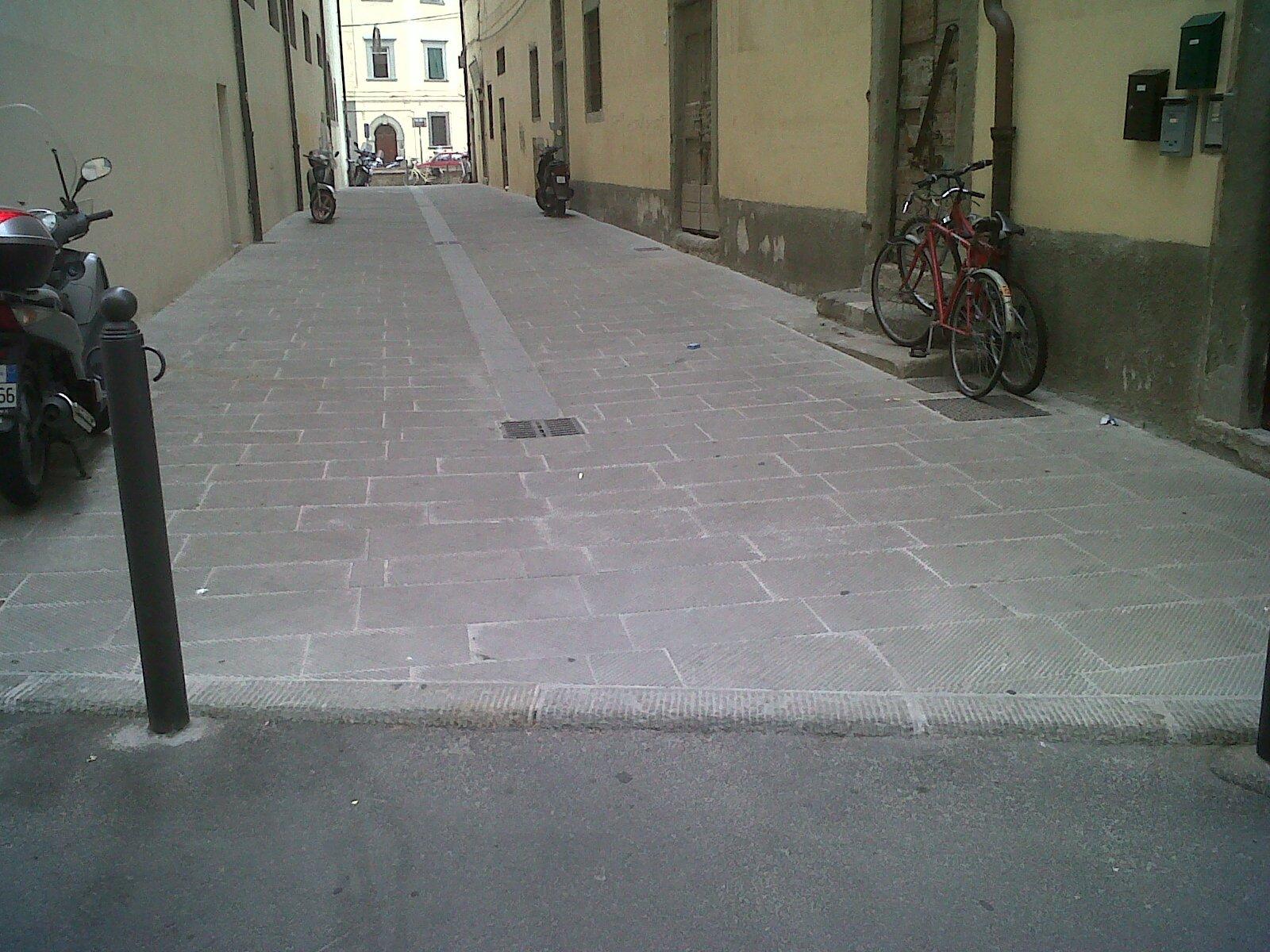 un asfaltazione in cemento in un vicolo con sulla destra due bici appoggiate al muro e sulla sinistra uno scooter