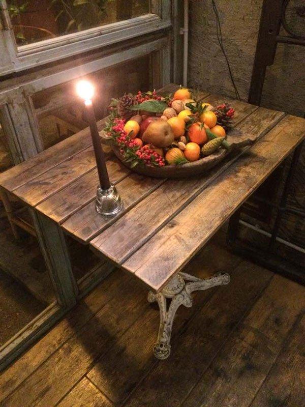 Tavolino in legno con cesto di frutta e candela accesa