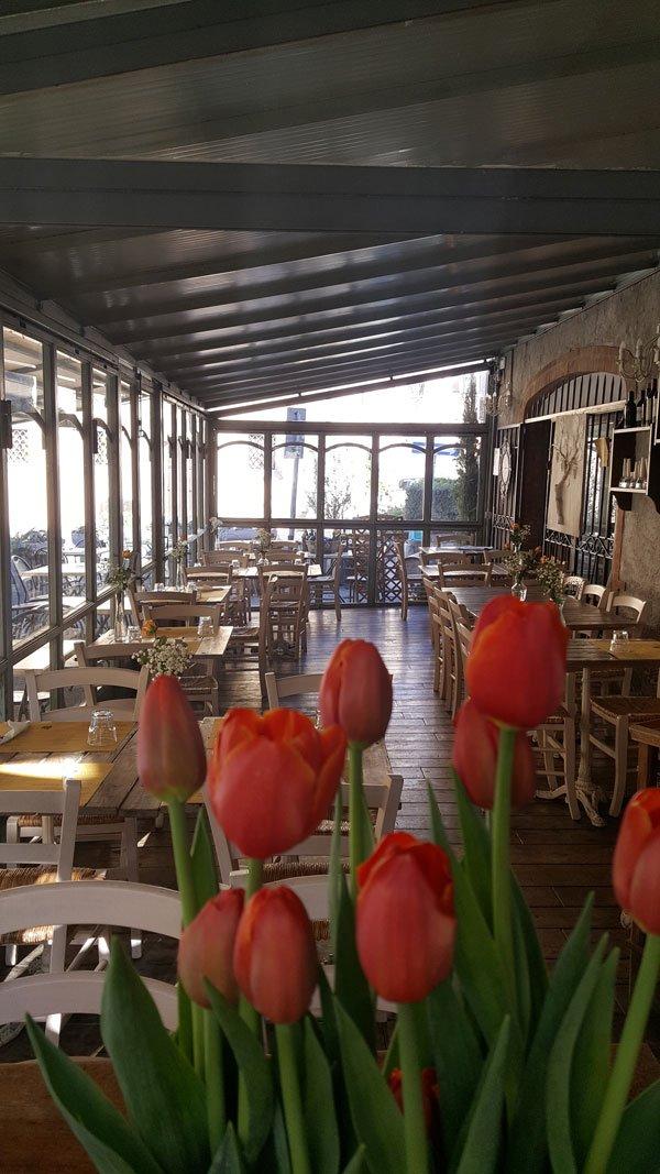 Tavolini all'esterno del locale e mazzo di tulipani