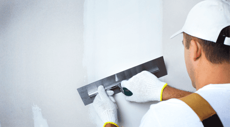 A wall being plastered white