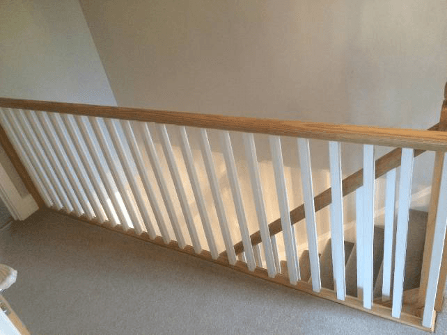 The top of a staircase with white and natural handrails