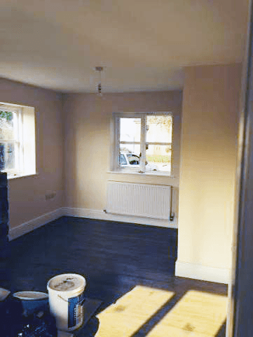 An empty room with pale walls, dark floor and two windows