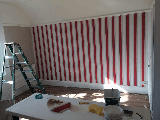 A stepladder and decorating materials in front of a red and white stripe wall