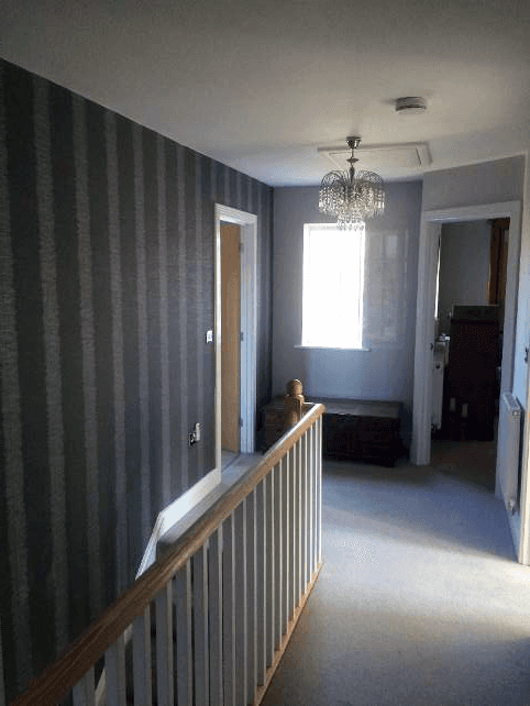 A landing with wooden rail, and dark brown stripe walls