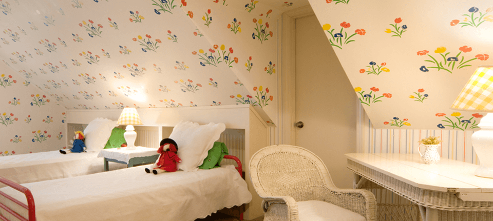Cream wallpaper patterned with colourful flowers in a child's bedroom with rag dolls on white twin beds