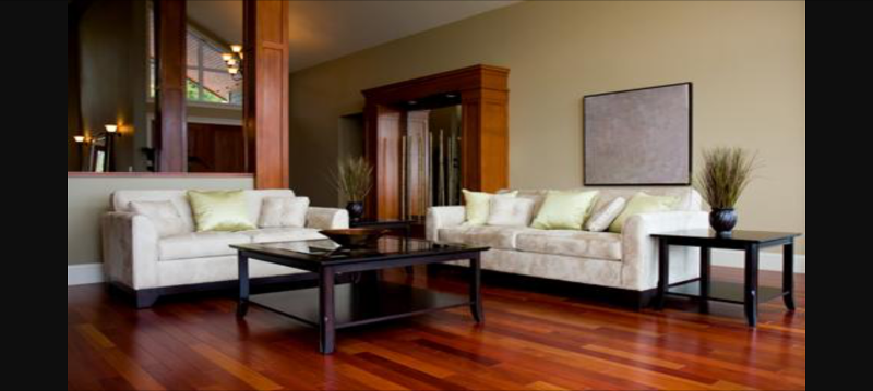 Two cream brocade sofas around a black square coffee table on a dark wood floor