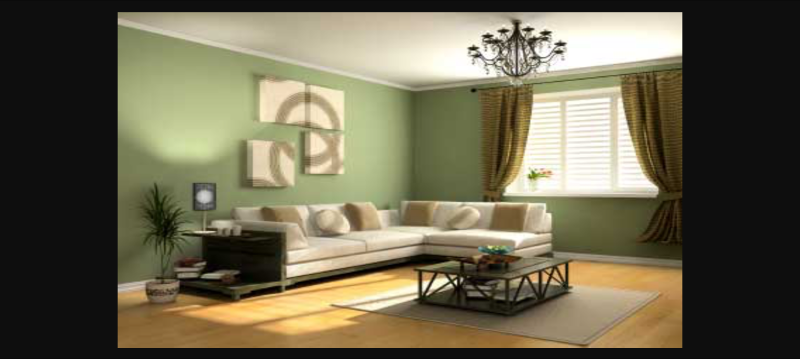 A cream L shaped corner sofa against a sage green wall, in a room with a central square coffee table on a beige rug