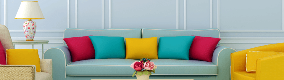 Red, turquoise and yellow cushions on an aqua sofa, next to a bright yellow tub chair, in front of pink roses in a pot on a coffee table
