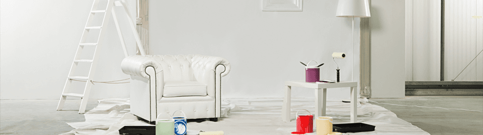 A white armchair, lamp and coffee table on a protective sheet, surrounded by pots of paint and a step ladder
