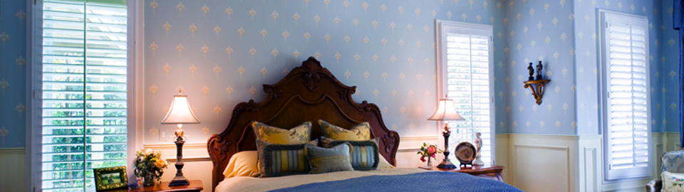 A bed with ornate timber bedhead, against a pale blue and white patterned wall, flanked by bedside tables with illuminated lamps