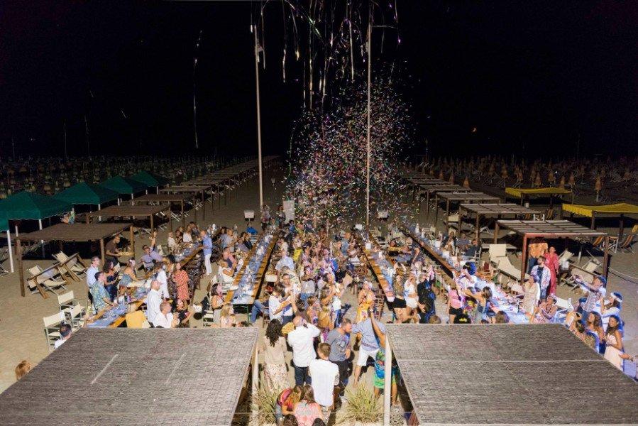 Vista notturna del luogo dove si vedono tutte le tavole occupate e gente in attesa per entrare