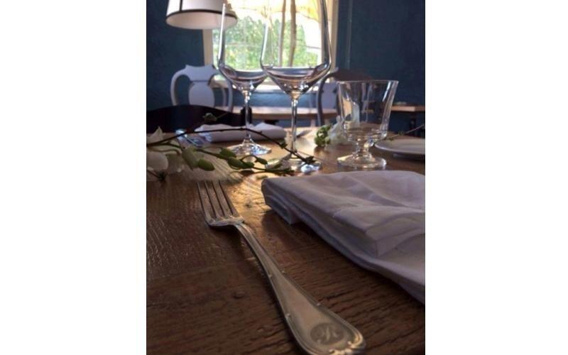 Dettaglio della tavola elenco con i piatti di porcellana bianca, coperti,bicchieri di vino