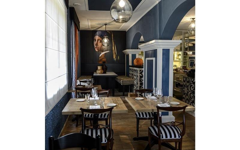 Vista del ristorante dove il legno dei mobili si combina con i colori blu e bianco di pareti e sedie e al fondo della riproduzione di una tabella del pittore VerMeer