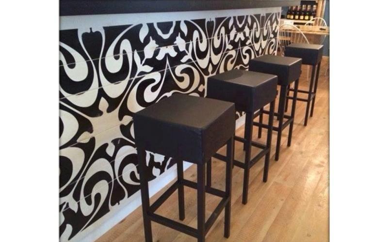 I sgabelli  del bar,quadrati e neri combinano con la decorazione del bar