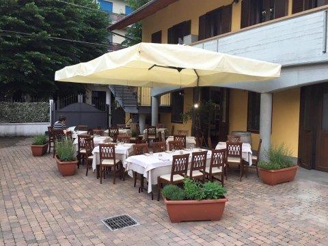 Esterno del ristorante con tavoli allestiti sotto l'ombrellone