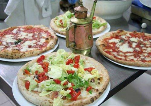 Due pizze bianche vegetali, una pizza di pomodoro e mozarella e una pizza di salame e mozzarella