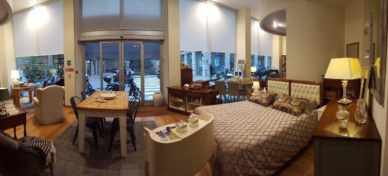 un letto matrimoniale e accanto un comò di legno e altri mobili