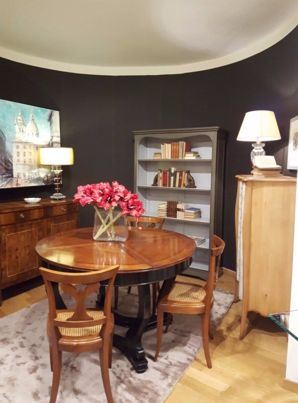 un tavolo di legno rotondo con delle sedie, un vaso di fiori e altri mobili accanto
