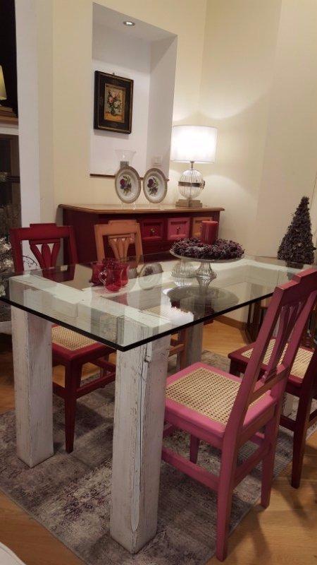 un tavolo di vetro con delle sedie di diversi colori