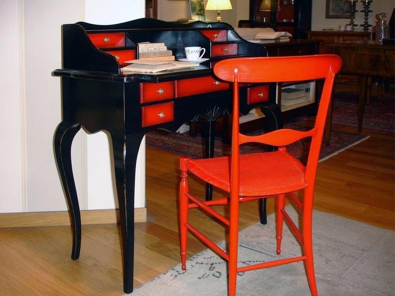 una sedia rossa e una scrivania nera con dei cassettini rossi
