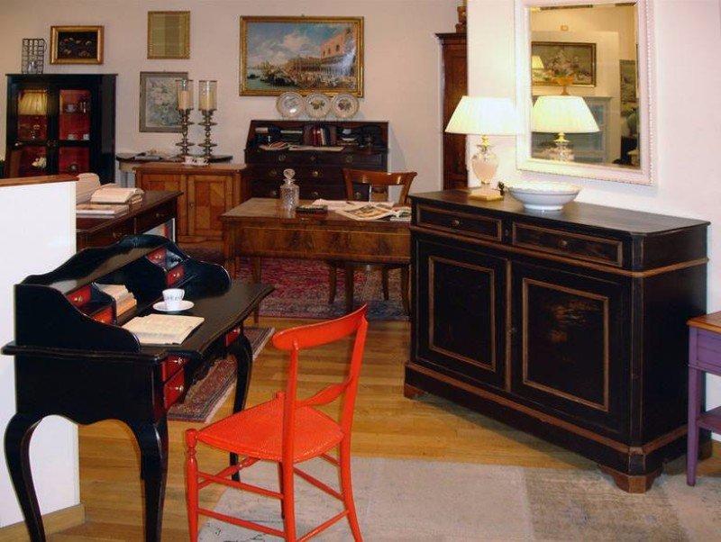 una sedia rossa e una scrivania nera con dei cassettini rossi e un mobile in legno con sopra una lampada