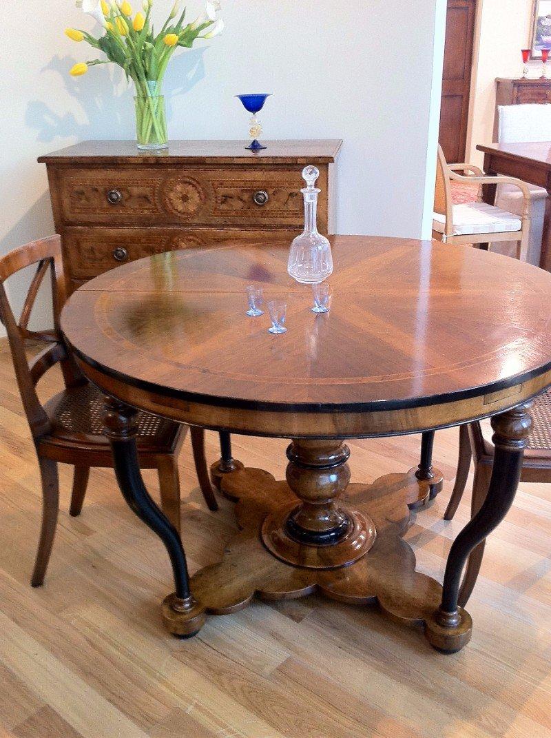 un tavolo rotondo in legno con sopra un campanello di cristallo