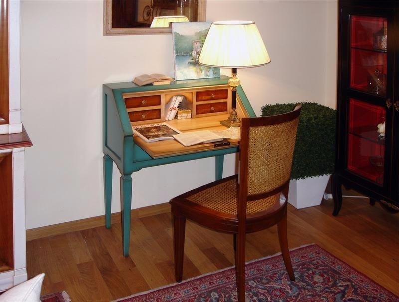 una scrivania antica di color turchese e davanti una sedia