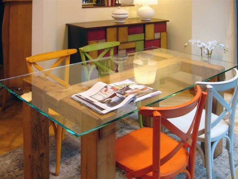 un tavolo di cristallo con delle sedie in legno di vari colori