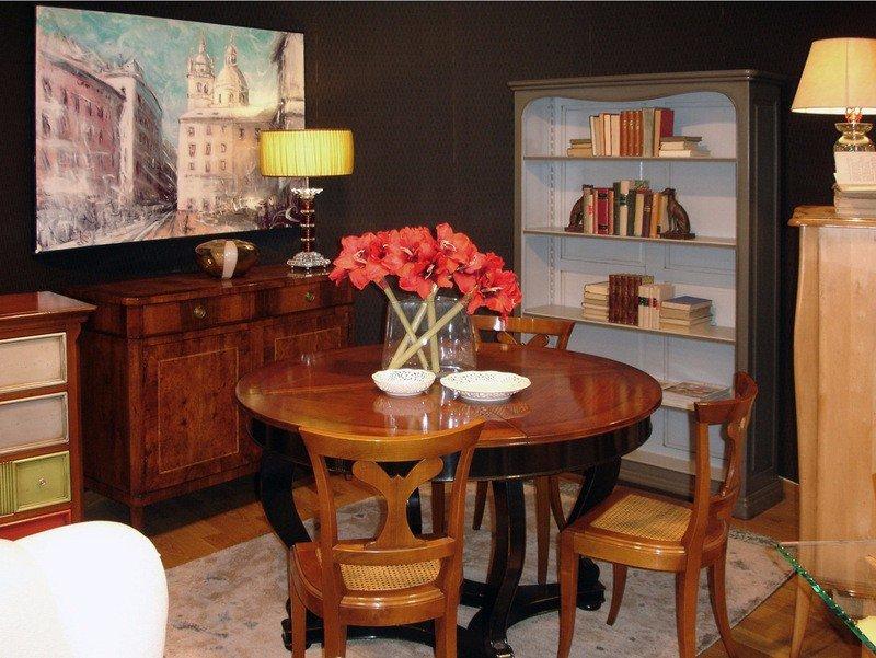 un tavolo rotondo in legno e accanto un como' e una libreria