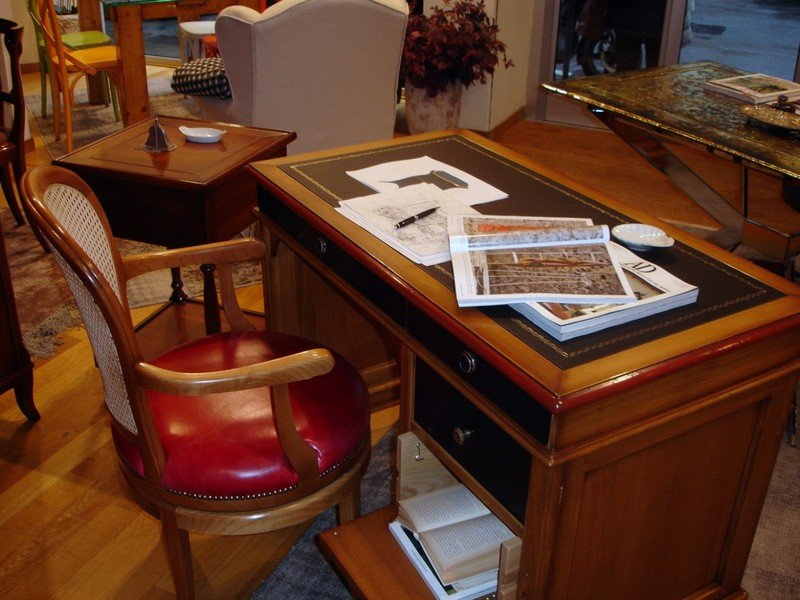 una scrivania e una sedia di legno con un cuscino imbottito di color fucsia