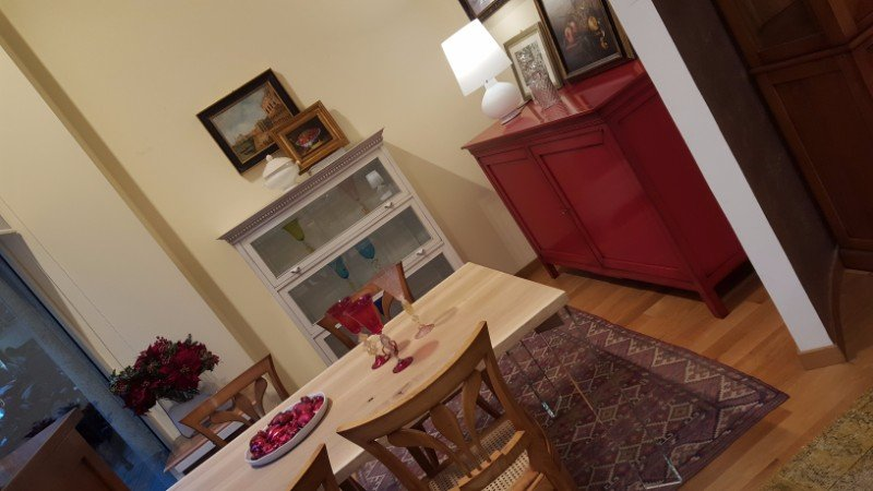un tavolo con delle sedie, sulla destra un mobile rosso con sopra una lampada e un mobiletto in legno bianco e vetro