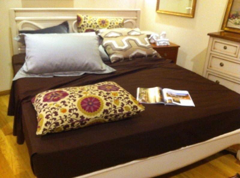 un letto con coprimaterasso marrone e cuscini di diversi colori