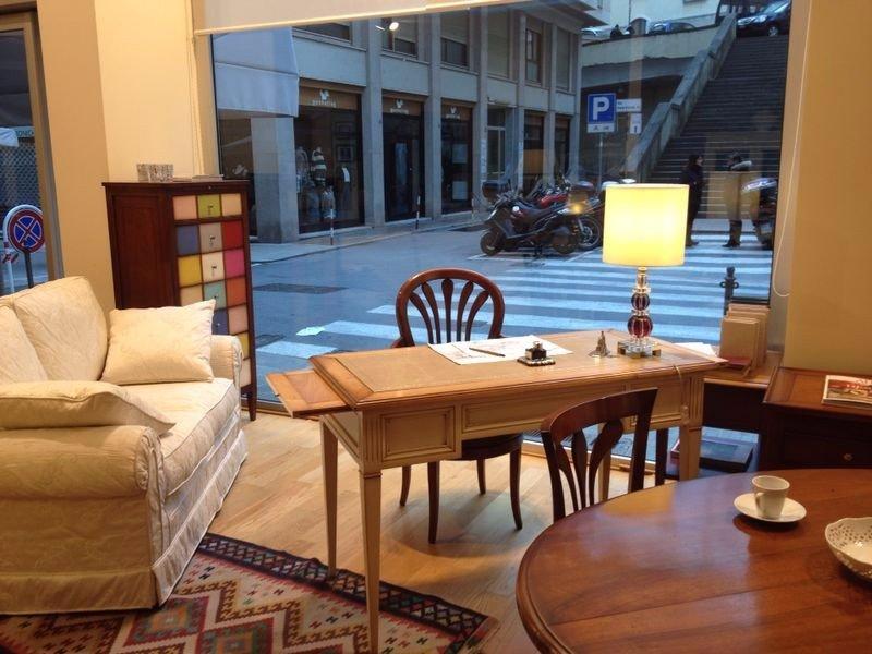 un tavolo rotondo, uno rettangolare, un divano, altri mobili e vista della vetrina e dell'esterno