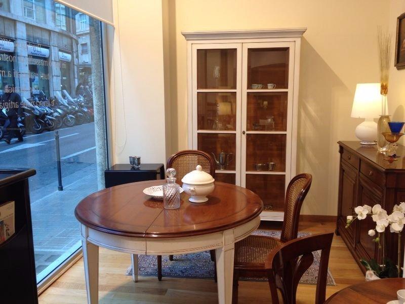 un tavolo marrone e bianco rotondo con delle sedie, un mobiletto marrone con sopra delle lampade e un armadio vetrina di color bianco