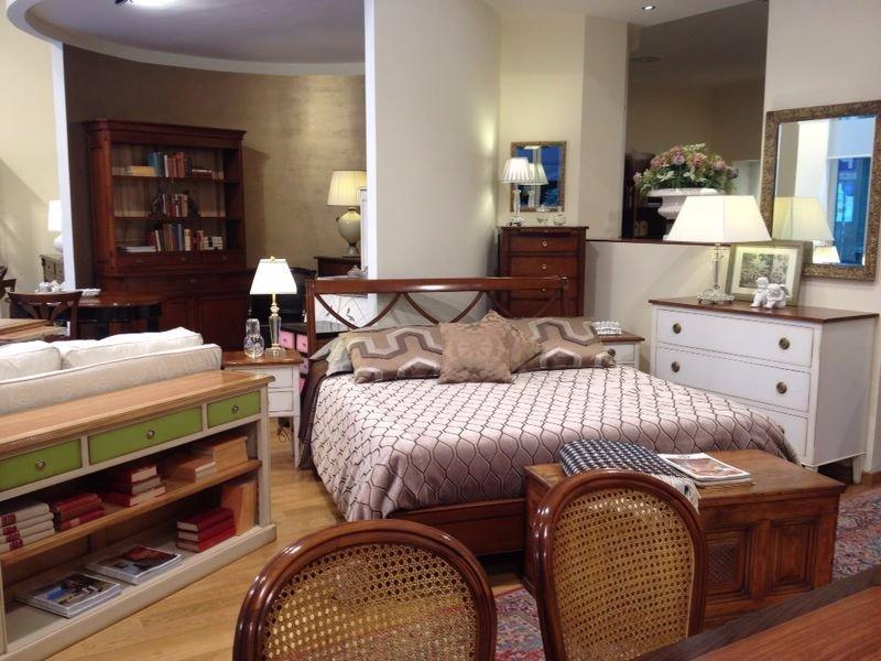 un letto, un como' con dei cassetti, sopra una lampada e altri mobili