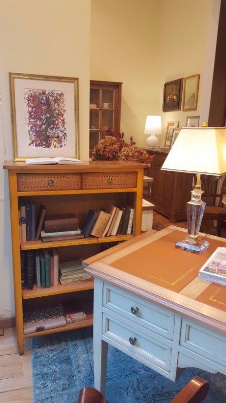una scrivania bianca con dei cassetti, sopra una lampada e un mobiletto in legno con delle mensole con sopra dei libri