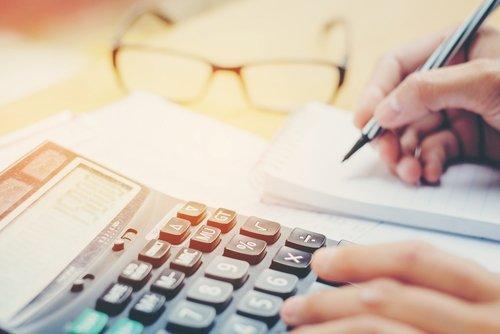 mano che fa calcoli con una calcolatrice