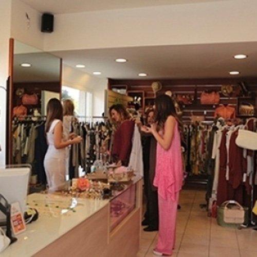 Clienti indossano abiti durante un evento presso la boutique