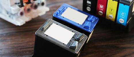 Due cartucce per stampante color nero e blu e accanto altre di color nero, rosso , giallo e azzurro