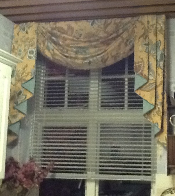 Yellow patterned curtains at a window with a white horizontal blind