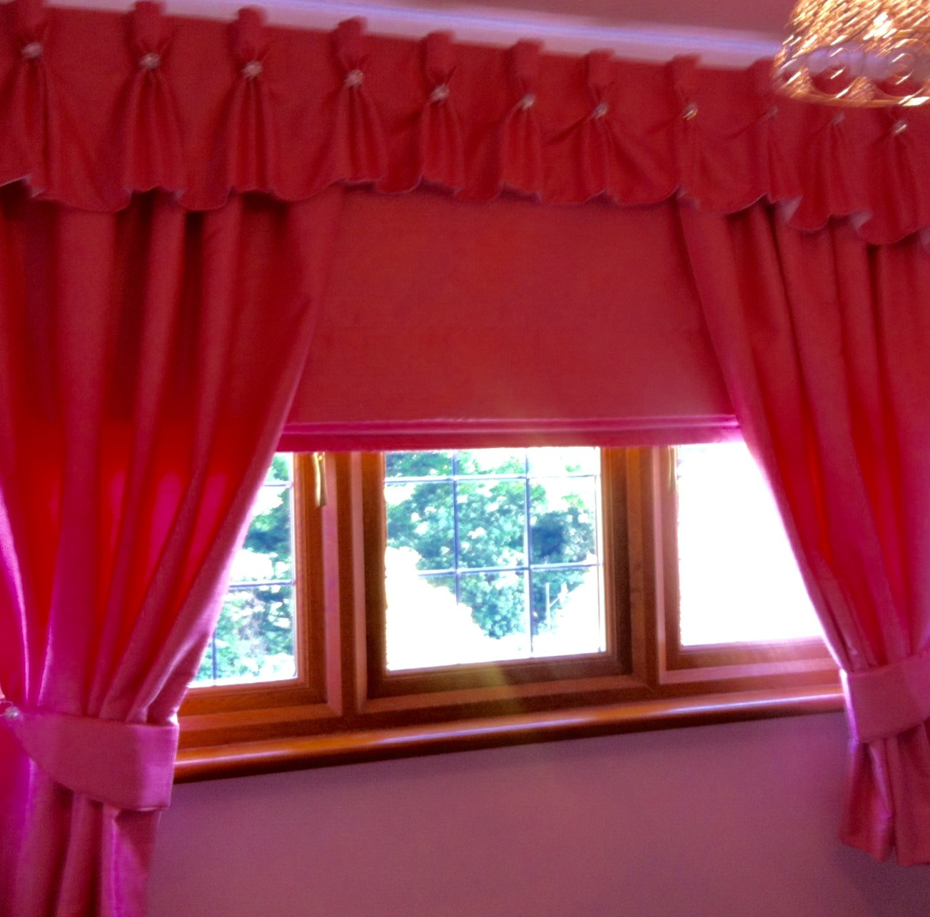 Deep red roller blind and curtains at a window with wooden frame