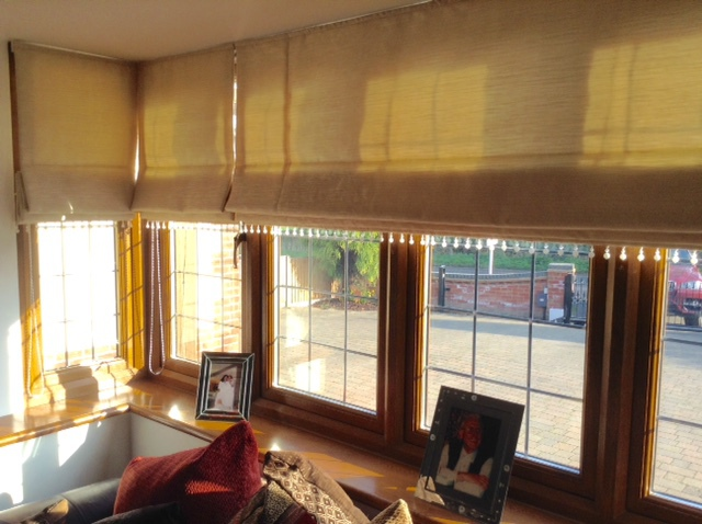 Velvet roller blind at a window with wooden frame and sills