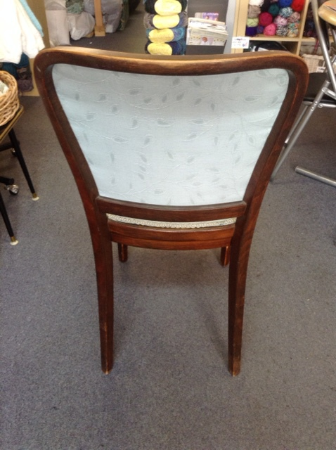 A white dining chair with wooden frame and legs