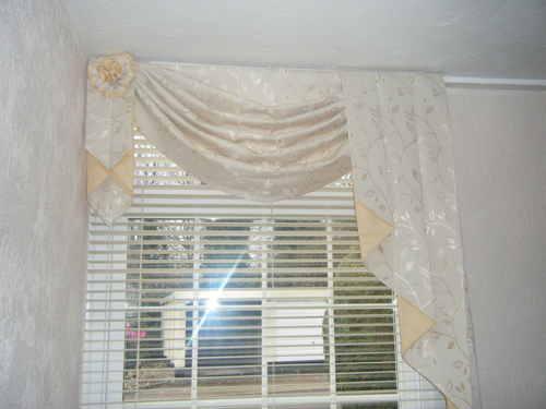 Swagged curtains at a window with horizontal blinds