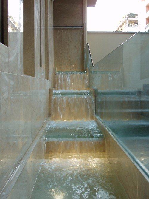 Fonte in forma di scale protetta da parapetto di vetro