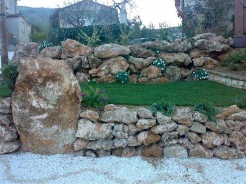 Le pietre di un piccolo muro che protegge l'erba e piccole Piante da fiori