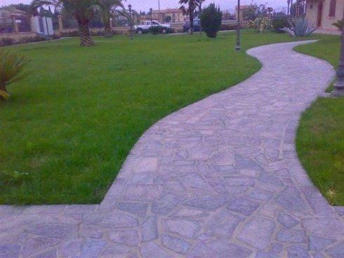 Cammino di lastre di pietra di accesso alla casa circondato di prato