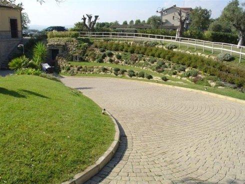 Cammino di pietra di stile antico con il giardino realizzato a gradini