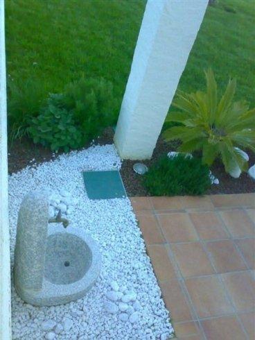Piccola sorgente di pietra di design moderno insieme a una parete della casa
